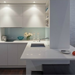 Small modern kitchen remodeling - Example of a small minimalist l-shaped dark wood floor kitchen design in New York with white cabinets, glass sheet backsplash, stainless steel appliances, an undermount sink, flat-panel cabinets, white backsplash and a peninsula