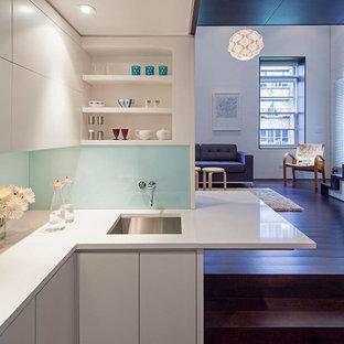 Bild på ett litet funkis kök, med en undermonterad diskho, släta luckor, vita skåp, glaspanel som stänkskydd, mörkt trägolv, rostfria vitvaror, vitt stänkskydd och en halv köksö