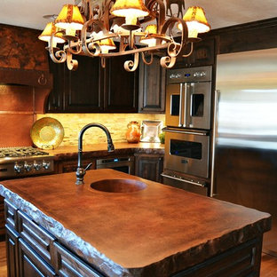 Inspiration for a large country u-shaped eat-in kitchen in Kansas City with a farmhouse sink, shaker cabinets, dark wood cabinets, concrete benchtops, beige splashback, stone tile splashback, stainless steel appliances, medium hardwood floors, multiple islands, brown floor and brown benchtop.
