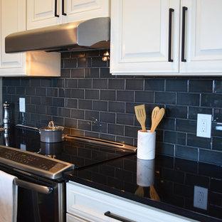 Immagine di una cucina abitabile tradizionale di medie dimensioni con lavello sottopiano, ante beige, top in rame, paraspruzzi nero, paraspruzzi con piastrelle in ceramica, elettrodomestici in acciaio inossidabile, parquet scuro e isola