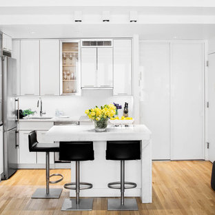 Small contemporary open concept kitchen pictures - Example of a small trendy l-shaped light wood floor and brown floor open concept kitchen design in New York with an undermount sink, flat-panel cabinets, white cabinets, marble countertops, white backsplash, stainless steel appliances and an island