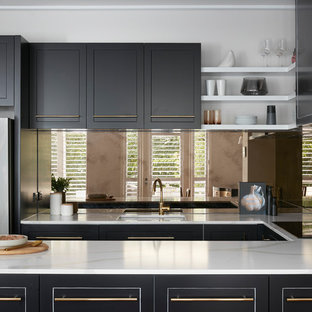 Photo of a large contemporary u-shaped kitchen in Melbourne with black cabinets, marble worktops, metallic splashback, a double-bowl sink, raised-panel cabinets, glass tiled splashback, coloured appliances, plywood flooring, an island, brown floors and white worktops.