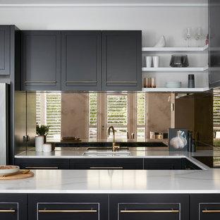 Esempio di una grande cucina contemporanea con ante nere, top in marmo, paraspruzzi a effetto metallico, lavello a doppia vasca, ante con bugna sagomata, paraspruzzi con piastrelle di vetro, elettrodomestici colorati, pavimento in compensato, un'isola, pavimento marrone e top bianco