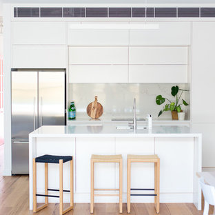 Design ideas for a mid-sized contemporary galley open plan kitchen in Sydney with an undermount sink, white cabinets, quartz benchtops, stainless steel appliances, light hardwood floors, with island, white benchtop, flat-panel cabinets, white splashback and brown floor.