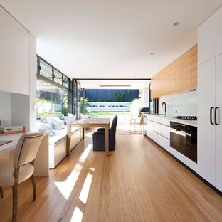 This is an example of a modern single-wall eat-in kitchen in Sydney with an undermount sink, flat-panel cabinets, quartz benchtops, white splashback, glass sheet splashback, black appliances, medium hardwood floors, no island, light wood cabinets and beige floor.