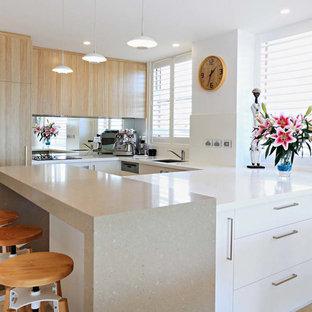 Diseño de cocina comedor en U, actual, pequeña, con armarios con paneles lisos, puertas de armario blancas, encimera de acrílico, suelo de travertino y península