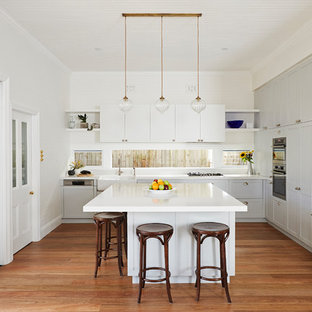 Mid-sized transitional l-shaped open plan kitchen in Sydney with a farmhouse sink, shaker cabinets, grey cabinets, solid surface benchtops, white splashback, window splashback, stainless steel appliances, with island and white benchtop.