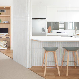 Mid-sized contemporary u-shaped kitchen in Sydney with a double-bowl sink, white cabinets, quartz benchtops, glass sheet splashback, stainless steel appliances, vinyl floors, no island, beige floor and white benchtop.