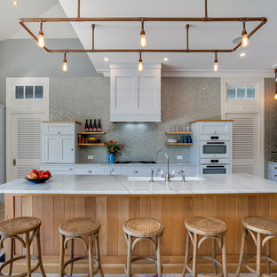 Photo of a beach style u-shaped kitchen in Melbourne with a farmhouse sink, shaker cabinets, white cabinets, grey splashback, white appliances and an island.