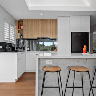 Mid-sized contemporary l-shaped open plan kitchen in Sydney with an undermount sink, flat-panel cabinets, white cabinets, quartz benchtops, metallic splashback, mirror splashback, stainless steel appliances, medium hardwood floors, with island, brown floor, white benchtop and vaulted.