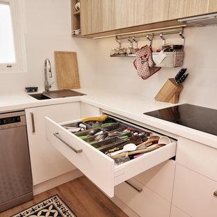 シドニーの中くらいのビーチスタイルのおしゃれなキッチン (シングルシンク、フラットパネル扉のキャビネット、白いキャビネット、人工大理石カウンター、白いキッチンパネル、セラミックタイルのキッチンパネル、シルバーの調理設備、クッションフロア、茶色い床) の写真