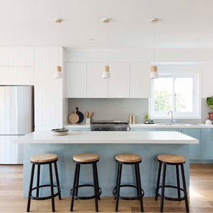 This is an example of a beach style l-shaped kitchen in Sydney with a double-bowl sink, flat-panel cabinets, blue cabinets, grey splashback, stainless steel appliances, medium hardwood floors, with island and brown floor.
