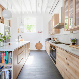 Photo of a contemporary galley kitchen/diner in London with light wood cabinets, marble worktops, grey splashback, marble splashback, ceramic flooring, an island, grey floors, grey worktops, a submerged sink, flat-panel cabinets and black appliances.
