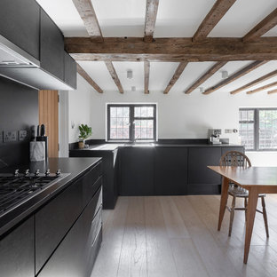 This is an example of a medium sized country l-shaped kitchen/diner in Oxfordshire with flat-panel cabinets, black cabinets, black splashback, light hardwood flooring, beige floors, black worktops and a submerged sink.