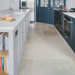 This is an example of a large farmhouse l-shaped kitchen/diner in Gloucestershire with a built-in sink, shaker cabinets, blue cabinets, engineered stone countertops, stainless steel appliances, limestone flooring, an island and grey worktops.
