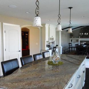 Diseño de cocina comedor en L, clásica renovada, con fregadero bajoencimera, puertas de armario amarillas, encimera de granito, salpicadero beige, salpicadero de piedra caliza, electrodomésticos de acero inoxidable, suelo de madera oscura y una isla