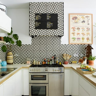 Medium sized bohemian u-shaped kitchen/diner in London with a double-bowl sink, flat-panel cabinets, white cabinets, wood worktops, white splashback, cement tile splashback, stainless steel appliances, painted wood flooring, a breakfast bar, white floors and white worktops.