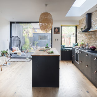 Mid-sized scandinavian single-wall kitchen in London with a double-bowl sink, flat-panel cabinets, black cabinets, wood benchtops, beige splashback, brick splashback, stainless steel appliances, light hardwood floors, with island and beige floor.