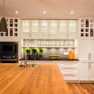 Idéer för att renovera ett mellanstort vintage svart svart kök, med en enkel diskho, skåp i shakerstil, vita skåp, träbänkskiva, vitt stänkskydd, glaspanel som stänkskydd, rostfria vitvaror, en köksö och brunt golv