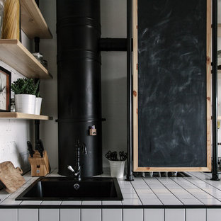 Idée de décoration pour une petite cuisine ouverte linéaire urbaine avec un évier encastré, un plan de travail en carrelage et un sol blanc.