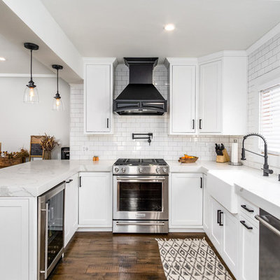 Elegant u-shaped dark wood floor and brown floor kitchen photo in San Diego with a farmhouse sink, shaker cabinets, white cabinets, white backsplash, subway tile backsplash, stainless steel appliances, a peninsula and white countertops
