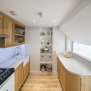Kitchen - small contemporary galley light wood floor kitchen idea in London with a farmhouse sink, shaker cabinets, light wood cabinets, marble countertops, white backsplash, subway tile backsplash, paneled appliances and no island