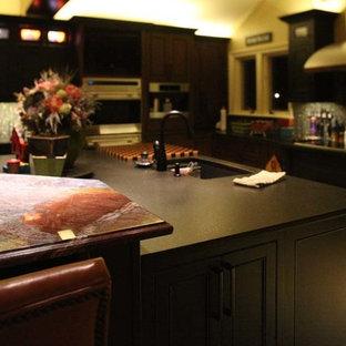 オースティンの大きいヴィクトリアン調のおしゃれなキッチン (ダブルシンク、レイズドパネル扉のキャビネット、濃色木目調キャビネット、御影石カウンター、グレーのキッチンパネル、セラミックタイルのキッチンパネル、シルバーの調理設備の、ライムストーンの床) の写真
