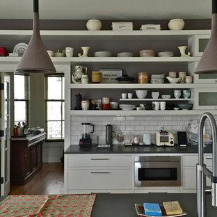 Inredning av ett modernt mellanstort linjärt kök med öppen planlösning, med en undermonterad diskho, släta luckor, vita skåp, bänkskiva i zink, vitt stänkskydd, stänkskydd i tunnelbanekakel, rostfria vitvaror, en köksö och mellanmörkt trägolv
