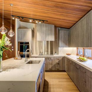 サンフランシスコのコンテンポラリースタイルのおしゃれなキッチン (アンダーカウンターシンク、フラットパネル扉のキャビネット、グレーのキャビネット、白いキッチンパネル、石スラブのキッチンパネル、シルバーの調理設備、無垢フローリング、茶色い床、白いキッチンカウンター) の写真