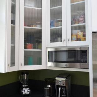 サンフランシスコの小さいエクレクティックスタイルのおしゃれなキッチン (アンダーカウンターシンク、シェーカースタイル扉のキャビネット、淡色木目調キャビネット、ラミネートカウンター、グレーのキッチンパネル、セメントタイルのキッチンパネル、シルバーの調理設備の、淡色無垢フローリング、黄色い床、黒いキッチンカウンター) の写真