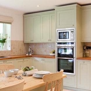 Ejemplo de cocina comedor clásica con encimera de madera, puertas de armario verdes, armarios estilo shaker, salpicadero beige y electrodomésticos de acero inoxidable