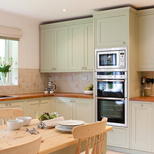 Inspiration for a traditional eat-in kitchen in Berkshire with wood benchtops, green cabinets, shaker cabinets, beige splashback and stainless steel appliances.
