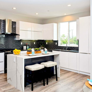 Mid-sized contemporary eat-in kitchen inspiration - Example of a mid-sized trendy u-shaped light wood floor and brown floor eat-in kitchen design in Orange County with flat-panel cabinets, white cabinets, quartz countertops, black backsplash, ceramic backsplash, black appliances, an island, black countertops and a double-bowl sink