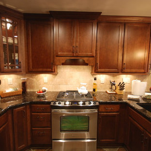 Example of a small classic u-shaped slate floor enclosed kitchen design in Other with an undermount sink, recessed-panel cabinets, medium tone wood cabinets, granite countertops, beige backsplash, stone tile backsplash and stainless steel appliances