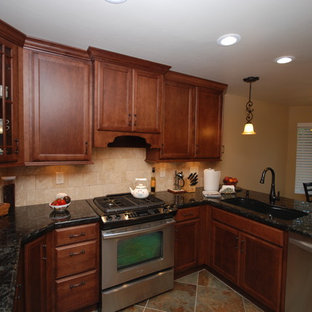 Small elegant u-shaped slate floor enclosed kitchen photo in Other with an undermount sink, recessed-panel cabinets, medium tone wood cabinets, granite countertops, beige backsplash, stone tile backsplash and stainless steel appliances
