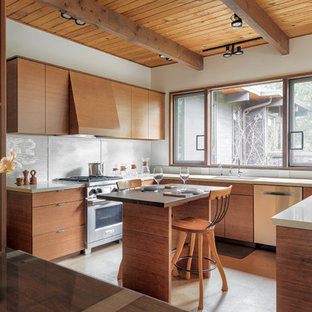 Midcentury modern kitchen remodeling - Kitchen - midcentury modern u-shaped gray floor kitchen idea in Seattle with an undermount sink, flat-panel cabinets, medium tone wood cabinets, white backsplash, glass sheet backsplash, stainless steel appliances, an island and white countertops