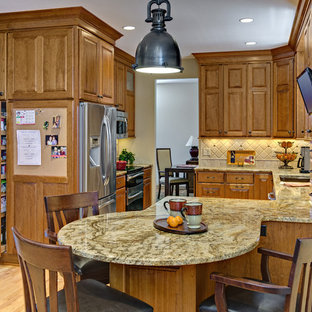Inspiration for a transitional u-shaped light wood floor kitchen pantry remodel in Minneapolis with a double-bowl sink, raised-panel cabinets, medium tone wood cabinets, granite countertops, beige backsplash, stone tile backsplash, stainless steel appliances and no island