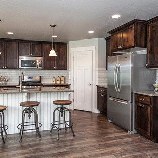 ソルトレイクシティの大きいインダストリアルスタイルのおしゃれなキッチン (ドロップインシンク、濃色木目調キャビネット、白いキッチンパネル、シルバーの調理設備の、濃色無垢フローリング、シェーカースタイル扉のキャビネット、御影石カウンター、サブウェイタイルのキッチンパネル、茶色い床) の写真
