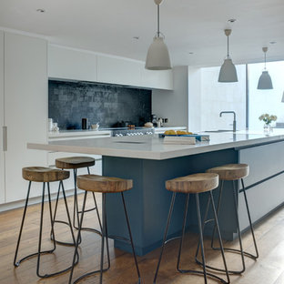 This is an example of an expansive contemporary single-wall open plan kitchen in London with an integrated sink, flat-panel cabinets, white cabinets, quartzite benchtops, black splashback, marble splashback, panelled appliances, medium hardwood floors, with island, beige floor and white benchtop.