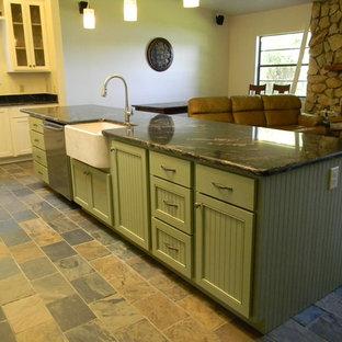 Ispirazione per una cucina american style di medie dimensioni con lavello stile country, ante a filo, ante verdi, top in granito, pavimento in ardesia, isola, pavimento arancione e top nero