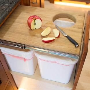 ミネアポリスの中くらいのおしゃれなキッチン (エプロンフロントシンク、インセット扉のキャビネット、中間色木目調キャビネット、クオーツストーンカウンター、ベージュキッチンパネル、磁器タイルのキッチンパネル、シルバーの調理設備、無垢フローリング) の写真