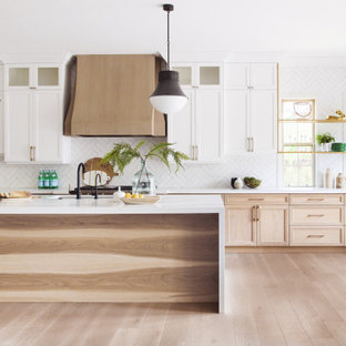 Esempio di una cucina classica con lavello sottopiano, ante con riquadro incassato, ante in legno chiaro, paraspruzzi bianco, elettrodomestici in acciaio inossidabile, pavimento in legno massello medio, pavimento marrone e top bianco