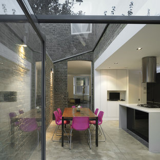Photo of a contemporary kitchen/diner in London with flat-panel cabinets, white cabinets, concrete flooring and an island.