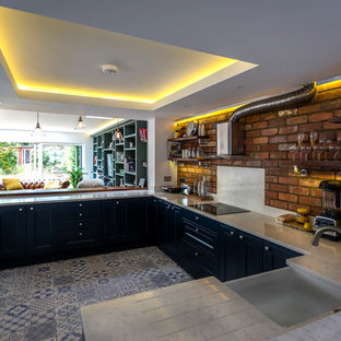 Mid-sized eclectic open concept kitchen designs - Mid-sized eclectic single-wall ceramic floor and blue floor open concept kitchen photo in Berkshire with a farmhouse sink, shaker cabinets, blue cabinets, quartzite countertops, red backsplash, brick backsplash, black appliances and a peninsula