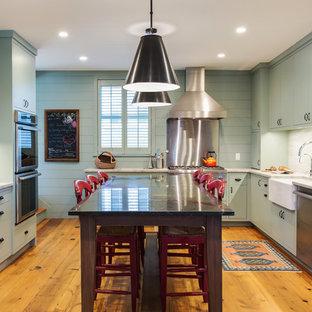 Ispirazione per una grande cucina country con lavello stile country, ante lisce, elettrodomestici in acciaio inossidabile, pavimento in legno massello medio, isola, ante verdi, paraspruzzi bianco, paraspruzzi in marmo e pavimento arancione