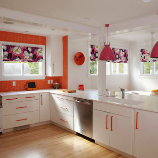 Design ideas for a large contemporary u-shaped eat-in kitchen in New York with an integrated sink, flat-panel cabinets, white cabinets, orange splashback, mosaic tile splashback, white appliances, solid surface benchtops, light hardwood floors and brown floor.