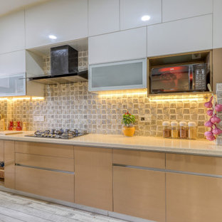 Photo of a mid-sized mediterranean galley kitchen in Bengaluru with flat-panel cabinets, beige cabinets, grey splashback, panelled appliances, no island, grey floor and beige benchtop.