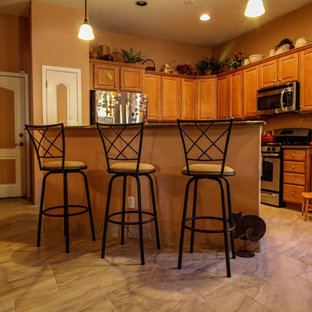 Example of a mid-sized transitional l-shaped porcelain floor kitchen design in Phoenix with raised-panel cabinets, light wood cabinets, stainless steel appliances and an island