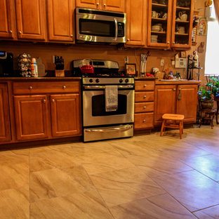 Inspiration for a mid-sized transitional l-shaped porcelain floor kitchen remodel in Phoenix with raised-panel cabinets, light wood cabinets, stainless steel appliances and an island