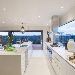 Ejemplo de cocina de galera, actual, abierta, con fregadero de doble seno, armarios con paneles lisos, puertas de armario blancas, electrodomésticos de acero inoxidable y una isla